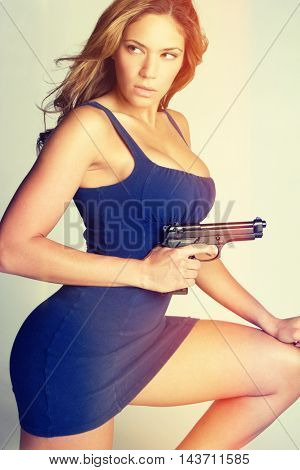 Sexy woman in dress holding gun
