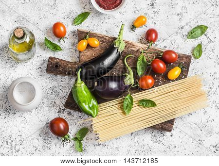 Cooking background. Raw ingredients for making pasta - spaghetti eggplant tomatoes pepper olive oil tomato sauce and basil on a rustic cutting board. Top view