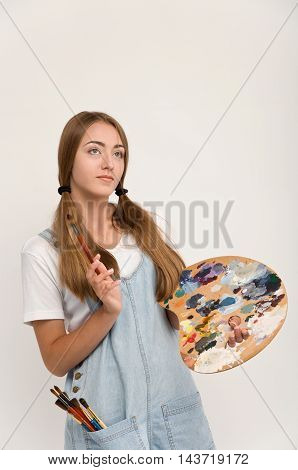 young artist holding a brush to paint and palette. creation