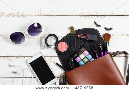 various makeup products and cosmetics in shoulder bag on white wooden background