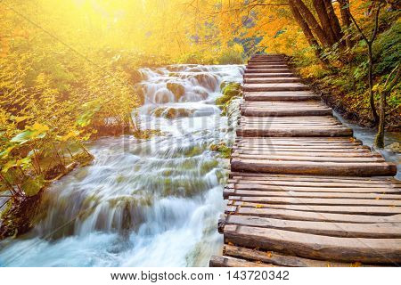 Scenic waterfalls and wooden path in a beautiful picturesque autumn scenery of the Plitvice Lakes National Park in Croatia, Europe