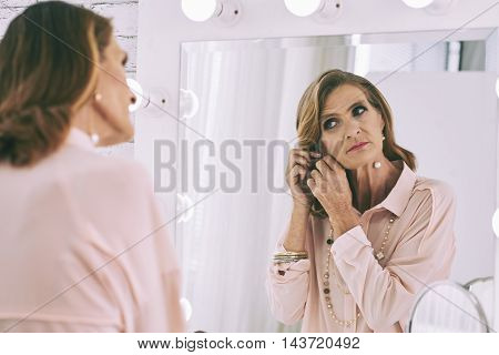 Mature woman getting ready in front of her vanity