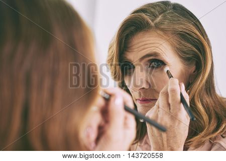 Close-up image of woman blending eyeshadows in front of mirror