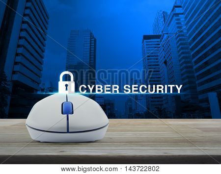 Wireless computer mouse with key icon and cyber security text on wooden table in front of city tower background