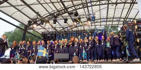 STOCKHOLM SWEDEN - AUG 21 2016: Happy swedish female soccer team waving swedish flags when the swedish olympic athletes are celebrated in Kungstradgarden Stockholm Sweden August 212016