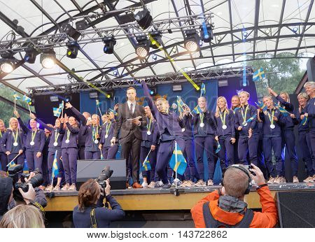 STOCKHOLM SWEDEN - AUG 21 2016: Happy swedish female soccer team waving swedish flags when the swedish olympic athletes are celebrated in Kungstradgarden, Stockholm, Sweden, August 21, 2016