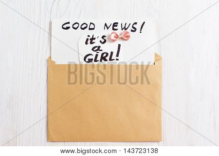 It's a girl card in brown envelope, flat lay. Greeting note with newborn child gender, mockup, white wooden background