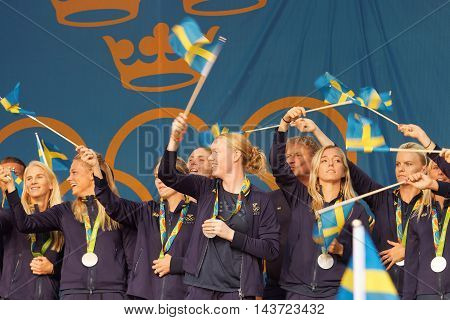 STOCKHOLM SWEDEN - AUG 21 2016: Happy swedish female soccer team waving swedish flags when the swedish olympic athletes are celebrated in Kungstradgarden Stockholm Sweden August 21 2016