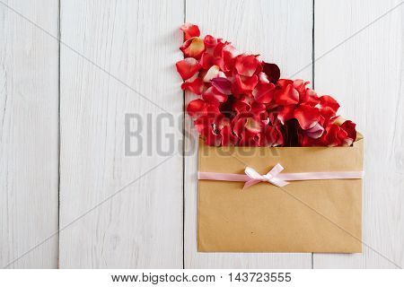 Brown envelope with red flower petals, copy space. Rose bloom getting out from paper pack on white wooden background, romantic greeting composition, flat lay