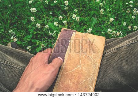 Old and tattered book on green background