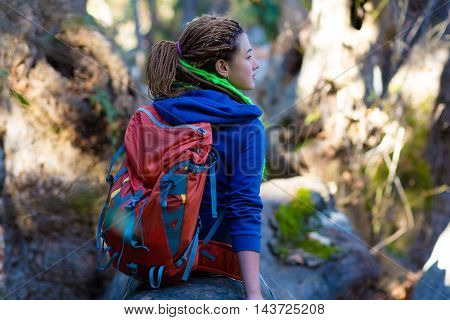 Girl with Backpack and Hippie style casual sporty clothing sitting on large trunk of a fallen Tree in Forest and enjoying Nature