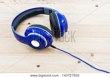 Blue headphones on the wood desk background.