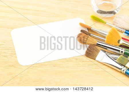 Group Of Watercolor Brush And Blank White Paper Card On Wood Table ,copy Space For Adding Your Conte