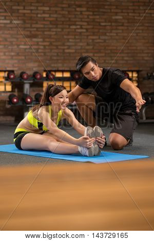 Young trainer explaining woman how to stretch