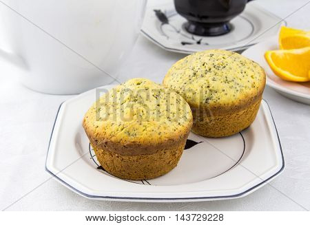 Photo of two orange poppy seed muffins on white plate