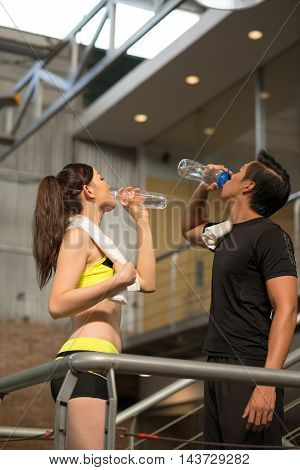 Asian couple drinking fresh water after training