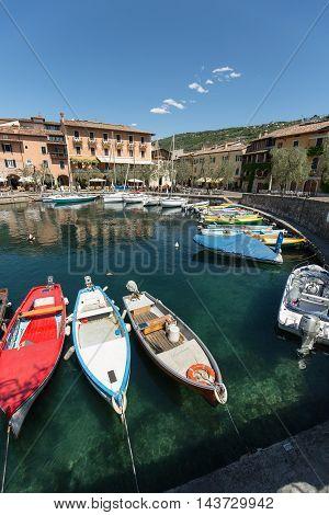 TORRI DEL BENACO, ITALY - MAY 4, 2016: A row of fishing boats in the small harbor of Torri del Benaco. Garda Lake. Italy