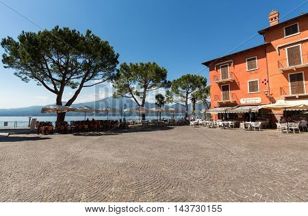 TORRI DEL BENACO, ITALY - MAY 4, 2016: Garda lake with promenade and restaurant in Torri del Benaco Italy
