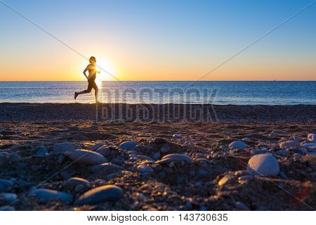 Human Silhouette jogging along Ocean Beach at Sunrise Pebble and Stones on foreground
