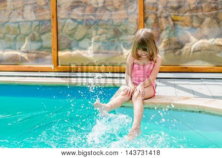 little girl sitting by the pool and having fun in the water feet