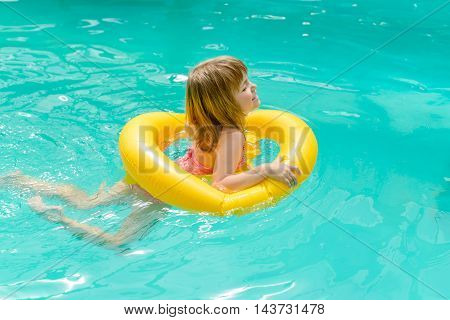 A little girl learning to swim with the help of an inflatable circle