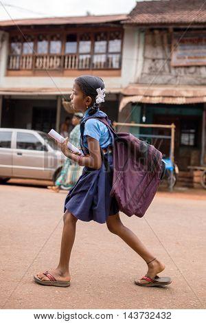 Gokarna, India - January 19, 2016: Unidentified indian girl with a heavy school bag go to school in Gokarna, India.
