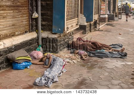 Mumbai, India - February 28, 2016: Unidentified  poor people sleep at the street in Mumbai, India. Over 90 million people in India have than 1 USD per day, setting them below global poverty threshold.