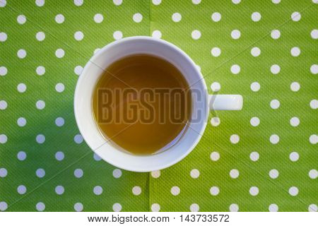 Cup of green tea on green spot background