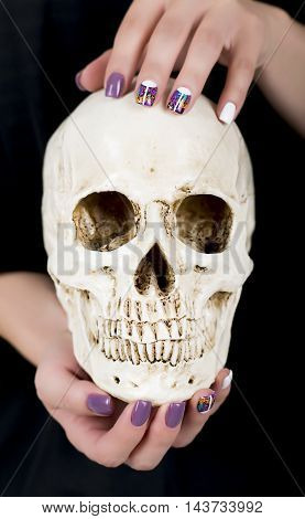 Hands with purple manicure holding human skull