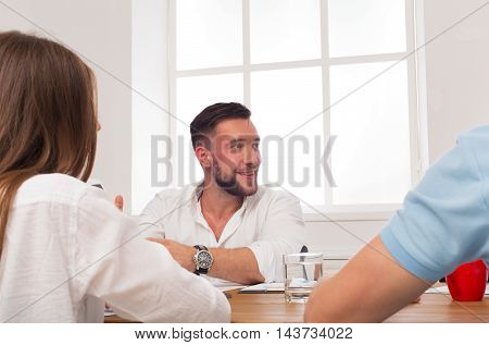 Business meeting. Young happy smiling businessman candid portrait at modern office, team corporate discussion at workplace. Communication with partners for startup