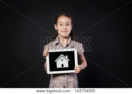 Little happy girl shows screen of white Digital Tablet with house icon. Female child studio portrait with modern device at black background, home for children and real estate buying concept
