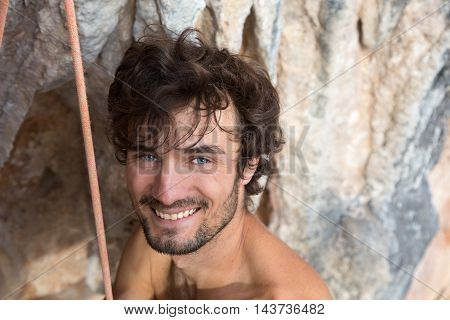 Portrait of Smiling Rock Climber Caucasian with curled Hair Style bearded holding Rope