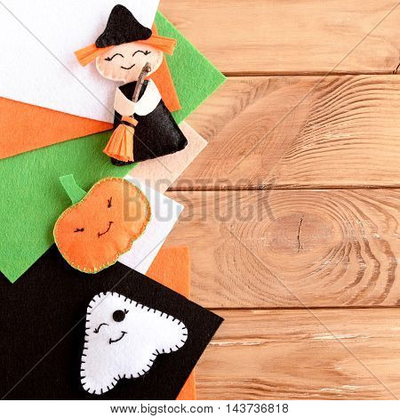 Pretty Halloween embellishments toys and felt sheets on wooden background with blank space for text. Little witch, pumpkin head and ghost made out of felt. Kids crafts. Halloween background