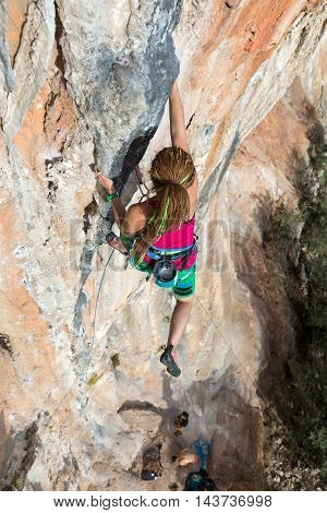 Female Climber Trying to keep Hold in last Effort to avoid deep fall down High rocky Wall orange blue Colors Rope and other Climbing Gear
