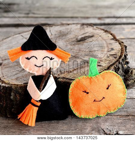 Halloween felt witch and pumpkin head near the stump. Wooden background. Homemade witch and pumpkin ornaments. Halloween crafts ideas for kids and beginners