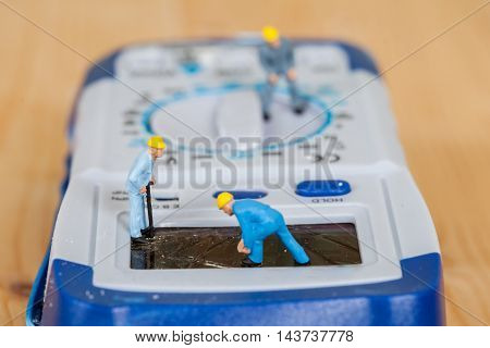 miniature maintenance team repairing a broken Digital multimeter