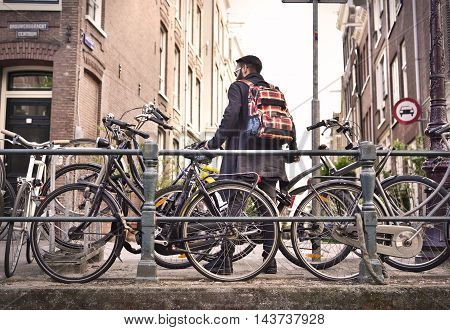 Young man with bicycles, Amsterdam city scene.