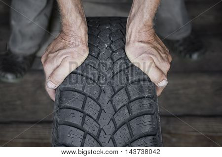 Hands of mechanic holding a tire with a winter tread in a garage indoor front shot with selective focus