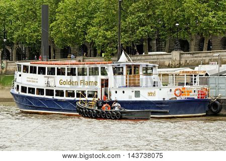 LONDON ENGLAND - JULY 8 2016: Golden Flame - a boat with 2 internal saloons and a large sundeck to hire for all types of family boat parties and celebrations on the Thames River.