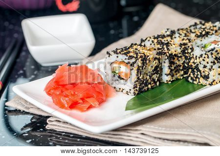 Salmon and black caviar rolls served on a plate on black background