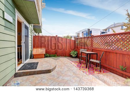 Backyard Area With Red Fence And Tile Flooring