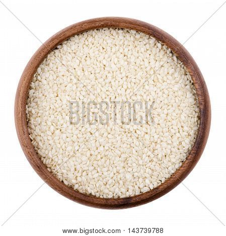 Sesame seeds in a wooden bowl on white background. Dried seeds with removed seed coats. Sesamum, also called benne. Edible, raw, organic and vegan food. Isolated macro photo close up from above.