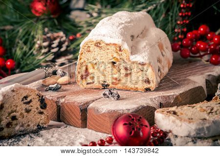 Stollen. Traditional German Christmas cake on a rustic festive table.