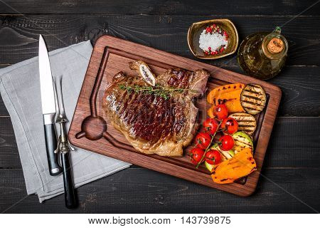 Club Beef steak with seasonings and Grilled vegetables on cutting board on dark wooden background, top view