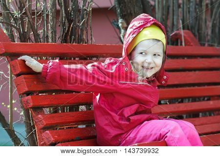 Smiling little girl leaning forward and sitting on red rest wood bench