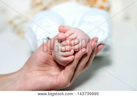 Mom holding baby feet on a white background