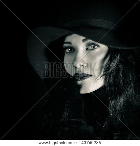 Beautiful, serious, calm woman, girl in big black hat, studio portrait, dark background. Attractive woman with bright amazing green eyes, red lips looking at camera. Black and white studio portrait