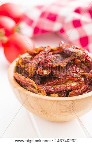 Tasty dried tomatoes in bowl on white table.