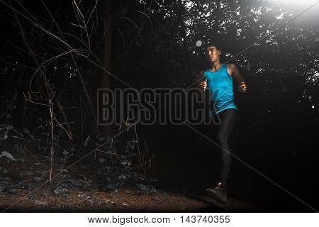 Athlete man running through dark forest