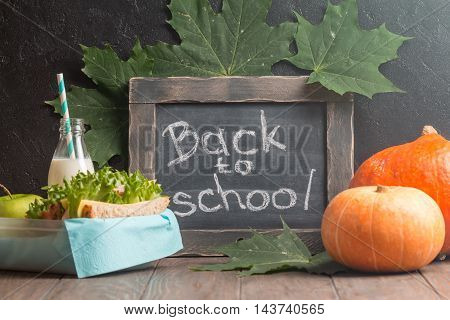 autumn still life with chalkboard, lunchbox and pumpkins on dark background